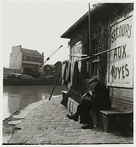 Roger-Viollet | 885524 | Old man smoking pipe in front of the station that provides help to drowning persons, la Villette pond, Paris (XIXth arrondissement). 1936. Photograph by Roger Schall (1904-1995). Paris, musée Carnavalet. | © Roger Schall / Musée Carnavalet / Roger-Viollet