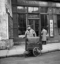 Roger-Viollet | 903665 | Man playing the barrel organ in front of the Roger-Viollet photo agency. Paris (VIth arrondissment), 6 rue de Seine, 1951. | © Roger-Viollet / Roger-Viollet