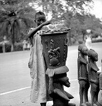 Roger-Viollet | 915221 | Boy playing the tom tom. Bouaké (Ivory Coast), February 1963. Photograph by Hélène Roger-Viollet (1901-1985). | © Hélène Roger-Viollet / Roger-Viollet