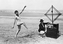 Roger-Viollet | 922887 | Miss Tamarys, from the théâtre de la Madeleine, dancing in front of a wireless radio set on the beach of Deauville, 1926. | © Roger-Viollet / Roger-Viollet