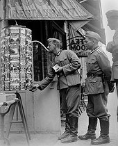 Roger-Viollet | 942718 | World War II. German soldiers buying postcards. Versailles, on August 19, 1940. | © LAPI / Roger-Viollet