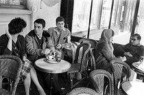 Roger-Viollet   959577   French director Claude Chabrol and the actors of his first two movies at the café  Les Deux-Magot : Bernadette Lafont, Gérard Blain, Jean-Claude Brialy and Juliet Mayniel. Paris, April 1959.   © Bernard Lipnitzki / Roger-Viollet