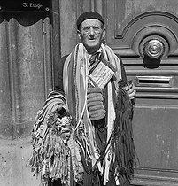 Roger-Viollet | 960284 | Guerre 1939-1945. Les petits métiers de Paris. Le vieux colporteur fait aujourd'hui concurrence aux Galeries Lafayette. Paris, 1943. Photographie d'André Zucca (1897-1973). Bibliothèque historique de la Ville de Paris. | © André Zucca / BHVP / Roger-Viollet