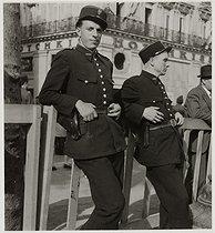 Roger-Viollet | 963382 | Two policemen on the avenue des Champs-Elysées. Paris (VIIIth arrondissement), 1945. Photograph by Roger Schall (1904-1995). Paris, musée Carnavalet. | © Roger Schall / Musée Carnavalet / Roger-Viollet