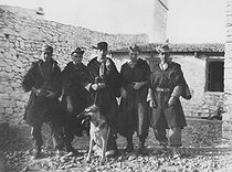 Roger-Viollet | 964098 | Algerian War of Independence. The French Army's fort in M'Zarouat, Mascara Area. The platoon included 48 harkis. The Sub-lieutenant Jean-Pierre Laffont, platoon commander, (in the middle) with his men and the fort's German shepherd. Algeria, Summer 1961. | © Jean-Pierre Laffont / Roger-Viollet
