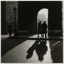 Roger-Viollet | 978353 | Three men in front of the porte Saint-Denis, boulevard Saint-Denis, Paris (Xth arrondissement). 1936. Photograph by Roger Schall (1904-1995). Paris, musée Carnavalet. | © Roger Schall / Musée Carnavalet / Roger-Viollet
