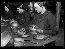 Roger-Viollet | 988222 | World War One. Workers of a French helmet manufacture, typical war industry. Adjusting of the crests. Photograph published in the newspaper  Excelsior , on January 29, 1916. | © Wackernie / Excelsior - L'Equipe / Roger-Viollet