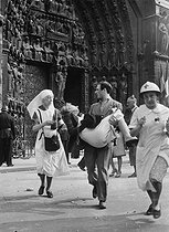 Roger-Viollet | 988489 | World War II. Liberation of Paris, first-aid worker carrying a wounded woman during a shooting at Notre-Dame de Paris, August 26, 1944. | © LAPI / Roger-Viollet