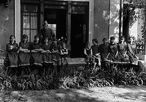 Roger-Viollet | 990586 | Photographic effect. Henri Roger and his 6 children. First from the left is Hélène Roger-Viollet at 17 years old, future founder of the Roger-Viollet agency. Henri Roger is wearing a uniform. Chatou, on June 30, 1918. | © Henri Roger / Roger-Viollet