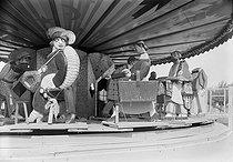 Roger-Viollet | 1005116 | Exposition des Arts décoratifs. Le manège de  la Vie Parisienne  réalisé par Paul Poiret en aval du pont Alexandre III. Paris, 1925. | © Albert Harlingue / Roger-Viollet
