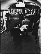 Roger-Viollet   1008088   Man reading the newspaper at the Gare-du-Nord metro station. Paris (Xth arrondissement), 1970. Photograph by Léon Claude Vénézia (1941-2013).   © Léon Claude Vénézia / Roger-Viollet