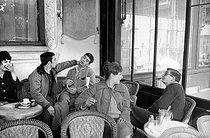 Roger-Viollet | 1020179 | French director Claude Chabrol and the actors of his first two movies at the café  Les Deux-Magot : Bernadette Lafont, Gérard Blain, Jean-Claude Brialy and Juliet Mayniel. Paris, April 1959. | © Bernard Lipnitzki / Roger-Viollet