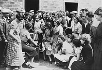 Roger-Viollet | 1029029 | Popular Front. Strikers listening to the wireless radio in the courtyard of the Lavalette manufacture. Saint-Ouen (France), 1936. | © Collection Roger-Viollet / Roger-Viollet