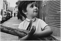 Roger-Viollet | 1035526 | Child carrying a baguette. Paris, 1971. Photograph by Janine Niepce (1921-2007). | © Janine Niepce / Roger-Viollet