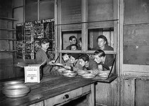 Roger-Viollet | 1040400 | World War II. Casein biscuit distribution in a Youth Centre. Paris, December 1941. | © LAPI / Roger-Viollet