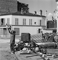 Roger-Viollet | 1042022 | World War II. Liberation of Paris. Statue holding the French flag and rubble, rue de Rungis. Paris (XIIth arrondissement), August 16-28, 1944. Photograph by André Zucca (1897-1973). Bibliothèque historique de la Ville de Paris. | © André Zucca / BHVP / Roger-Viollet