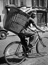 Roger-Viollet | 1048725 | Apprentice baker on a bicycle. France, 1938. | © Roger-Viollet / Roger-Viollet
