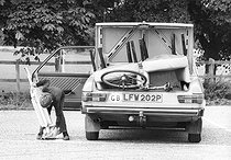 Roger-Viollet | 1049322 | Boy putting a vacuum cleaner in the boot of a car. United Kingdom, 1970's. | © Jean-Pierre Couderc / Roger-Viollet