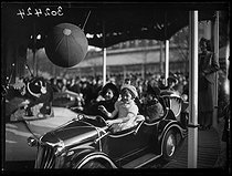 Roger-Viollet | 1056328 | Spring sale of gingerbread at the Foire du Trône fun fair. Children in bumper cars. Paris, on April 9, 1939. Photograph from the collections of the newspaper  Excelsior . | © Excelsior - L'Equipe / Roger-Viollet