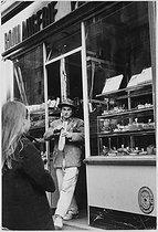 Roger-Viollet | 1058647 | Man leaving a bakery. Paris, 1960's. Photograph by Janine Niepce (1921-2007). | © Janine Niepce / Roger-Viollet