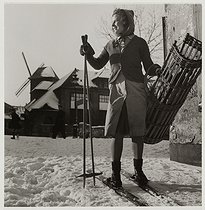 Roger-Viollet | 1070351 | World War II. Young girl carrying bread on skis, windmill in a snowy street, Montmartre, Paris (XVIIIth arrondissement). 1941. Photograph by Roger Schall (1904-1995). Paris, musée Carnavalet. | © Roger Schall / Musée Carnavalet / Roger-Viollet