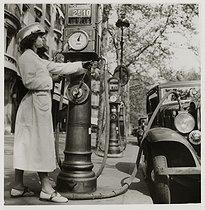 Roger-Viollet | 1071460 | Female pump attendant filling a car petrol tank, boulevard Haussmann. Paris (IXth arrondissement). 1936. Photograph by Roger Schall (1904-1995). Paris, musée Carnavalet. | © Roger Schall / Musée Carnavalet / Roger-Viollet