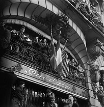 Roger-Viollet   1075076   World War II. Liberation of Paris. English, French and American flags at the entrance of the Guerlain shop, during the parade on the avenue des Champs-Elysées. Paris (VIIIth arrondissement), on November 11, 1944. Photograph by Pierre Jahan (1909-2003).   © Pierre Jahan / Roger-Viollet