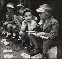 Roger-Viollet | 1078631 | Children wearing caps of the newspaper  La Vie Ouvrière . Leaflets announcing that the French politician Maurice Thorez is fine. Paris, 1950. Photograph by Janine Niepce (1921-2007). | © Janine Niepce / Roger-Viollet