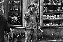 Roger-Viollet | 1081620 | Man in front of a bakery, rue de Sèvres. Paris, 1963. Photograph by Janine Niepce (1921-2007). | © Janine Niepce / Roger-Viollet