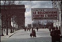 Roger-Viollet | 1095077 | World War II. Poster on the Champs-Elysées, Paris. Photograph by André Zucca (1897-1973). Bibliothèque historique de la Ville de Paris. | © André Zucca / BHVP / Roger-Viollet