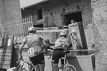 Roger-Viollet | 1351341 | Tour de France 1971. 10th stage from Saint-Etienne to Grenoble, on July 7, 1971. French racing cyclists Georges Chappe (born in 1944), bib number 41, and Charly Grosskost (1944-2004), bib number 94, refreshing themselves. Photograph by Bernard Charlet, from the collections of the French newspaper  France-Soir . Bibliothèque historique de la Ville de Paris. | © Bernard Charlet / Fonds France-Soir / BHVP / Roger-Viollet