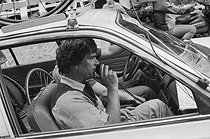 Roger-Viollet | 1358711 | Tour de France 1985. Bernard Tapie (born in 1943), French businessman and politician, aboard a car during the 8th stage from Sarrebourg to Strasbourg (France), on July 6, 1985. Photograph by Bernard Charlet, from the collections of the French newspaper  France-Soir . Bibliothèque historique de la Ville de Paris. | © Bernard Charlet / Fonds France-Soir / BHVP / Roger-Viollet