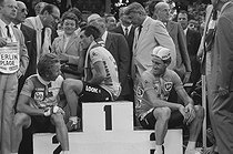 Roger-Viollet | 1359938 | Tour de France 1985. Bernard Hinault (born in 1954), French racing cyclist and winner of the Tour, surrounded by Greg LeMond and Sean Kelly, at the finish on the avenue des Champs-Elysées. Paris (VIIIth arrondissement), on July 21, 1985. Photograph by Bernard Charlet, from the collections of the French newspaper  France-Soir . Bibliothèque historique de la Ville de Paris. | © Bernard Charlet / Fonds France-Soir / BHVP / Roger-Viollet