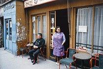 Roger-Viollet | 1372394 | Belleville district. Man and woman in front of a café, next to a cobbler's shop. Paris (XIXth arrondissement), 1968-1975. Photograph by François-Xavier Bouchart (1946-1993). Paris, musée Carnavalet. | © François-Xavier Bouchart / Musée Carnavalet / Roger-Viollet