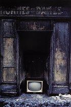 Roger-Viollet | 1372426 | Belleville district. TV set on the floor of a former hair salon. Paris (XIXth-XXth arrondissements), 1968-1975. Photograph by François-Xavier Bouchart (1946-1993). Paris, musée Carnavalet. | © François-Xavier Bouchart / Musée Carnavalet / Roger-Viollet