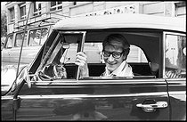 Roger-Viollet | 1376355 | Yves Saint-Laurent (1936-2008), French top designer, costume designer and businessman, at the wheel of his car, a convertible Coccinelle Volkswagen. Paris, 1977. Photograph by André Perlstein (born in 1942). | © André Perlstein / Roger-Viollet