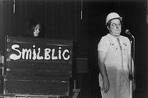 Roger-Viollet | 1376641 | Coluche (1944-1986), French humorist and actor, performing his famous humorous sketch  Schmilblic . 1975. Photograph by André Perlstein (born in 1942). | © André Perlstein / Roger-Viollet