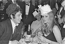 Roger-Viollet   1385003   Jean-Paul Belmondo (1933-2021), French actor, and Ursula Andress (born in 1936), Swiss actress, celebrating the New Year's Eve, on January 1st, 1968. Photograph by Claude Poensin-Burat,from the collections of the French newspaper France-Soir. Bibliothèque historique de la Ville de Paris.   © Poensin-Burat, Claude / Fonds France-Soir / BHVP / Roger-Viollet
